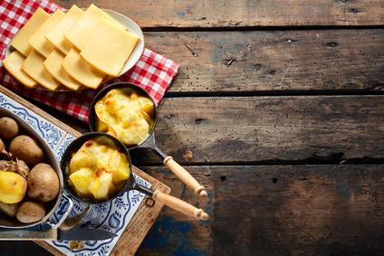 köstlicher geschmolzener Raclettekäse auf Kartoffeln